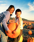 USA, California, girl and boy carrying a pumpkin at Bob's Pumpkin Patch, Half Moon Bay