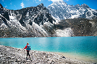 A woman trekker hikes alongside one of the lakes at Gokyo, Nepal