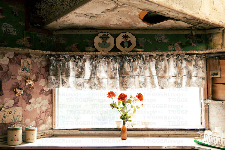 Interior view of old, dirty kitchen window with flowers and lace decoration