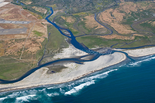 Aerial view of the Tijuana River mouth breaking through a sandbar and entering the Pacific Ocean, looking east.