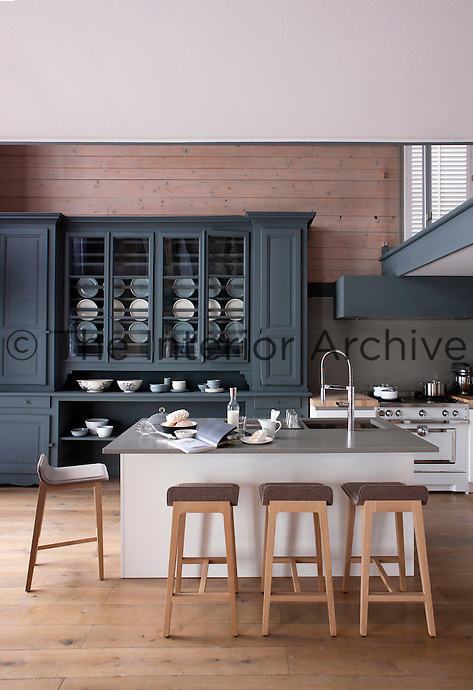 A contemporary grey-painted wooden dresser dominates the larch-clad wall of the open plan kitchen area