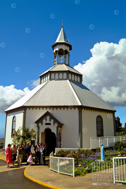 A bride, groom, their children, parents and wedding party outside historical Holy Ghost church, community of Kula, on the slopes of dormant Haleakala volcano, Upcountry Maui