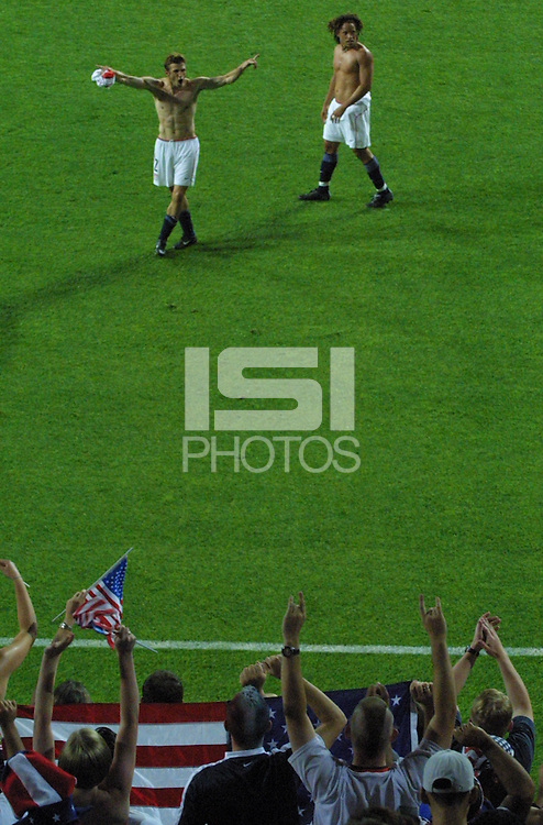 United States national team player (left to right) Frankie Hedjuk and Cobi Jones cheer with American supporters after the USA-Poland first round World Cup match in Daejon, South Korea on June 14th, 2002.  Poland defeated the United States 3-1. However, with South Korea's 1-0 victory over Portugal, the USA advanced to the second round of the World Cup.