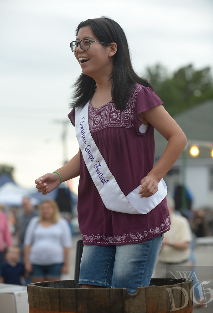 NWA Democrat-Gazette/ANDY SHUPE<br /> Sophia Miller, who will be officially crowned the 120th Queen Concordia Friday, laughs Wednesday, Aug. 8, 2018, as she stomps grapes in a barrel during the 120th annual Tontitown Grape Festival in Tontitown. The festival continues through Saturday. The festival features a nightly midway, an arts and crafts fair, spaghetti dinners and live entertainment.