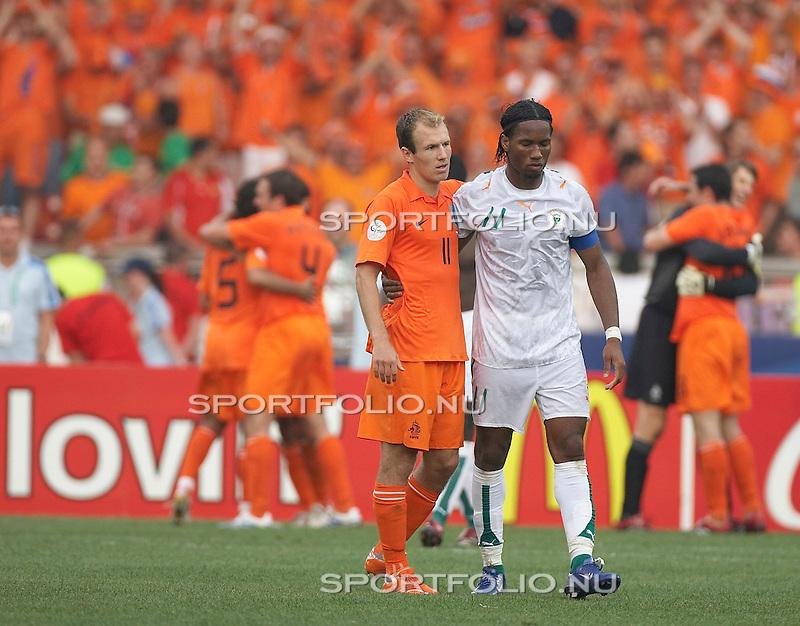 Duitsland, Stuttgart, 16 juni 2006. .WK voetbal 2006 .Groep C .Nederland-Ivoorkust (2-1). .Arjen Robben van Nederland slaat de arm om zijn ploeggenoot bij Chelsea Didier Drogba van Ivoorkust na afloop van de wedstrijd.