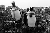 Italy. Lazio region. Rome. The Colosseum. Two tourists carry on their back penguins and photo cameras. The Colosseum, or the Coliseum, originally the Flavian Amphitheatre (Colosseo), is an elliptical amphitheatre in the centre of the city of Rome, the largest ever built in the Roman Empire. It is considered one of the greatest works of Roman architecture and Roman engineering. 10.2.1991 © 1991 Didier Ruef