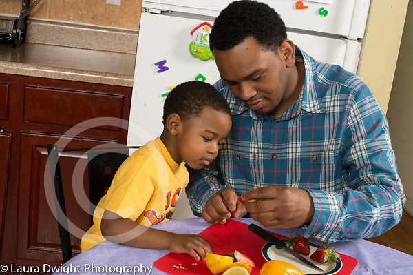 3 year old boy at home with father, in kitchen, learning about fruits and vegetables interested in sweet pepper they cut