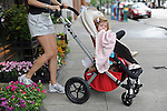 A woman leaves the New Leaf florist with her baby in one of the large strollers that locals say are a trend characteristic of Lincoln Park and Old Town on North Wells Street, the main shopping thoroughfare in Old Town, in Chicago, Illinois on June 19, 2009.