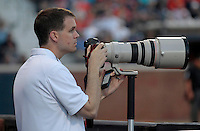 Virginia twitter photographer Matt Riley pulls double duty during the game against Clemson Friday at Davenport Field in Charlottesville, VA. Photo/The Daily Progress/Andrew Shurtleff