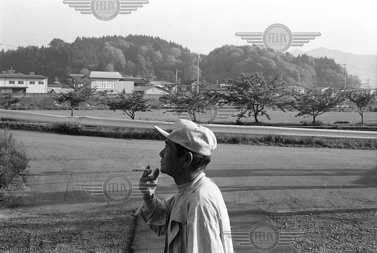 An elderly man enjoys a cigarette whilst he waits for the first train of the day, outside of Orikasa Station, Yamada Township.