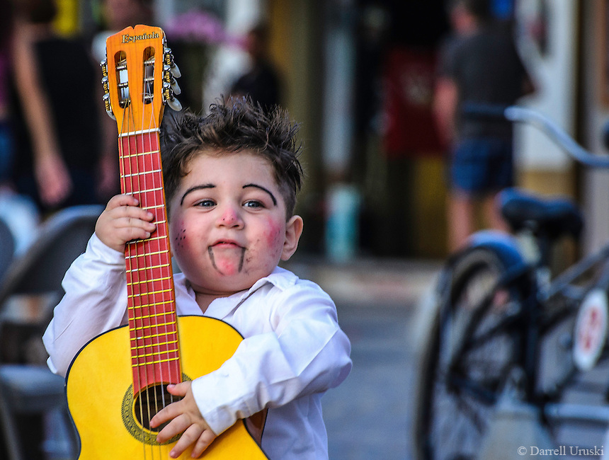 Urban Street Photograph of a young clown playing his guitar on the street in Puerto Vallarta, Mexico.