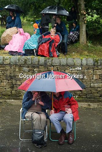 August summer rain. Visitors watch Morris men dance during a rain storm. Uppermill Saddleworth Yorkshire UK 2012