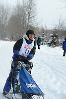 Greg Taylor passes by University Lake during the first day of the World Championship Sled Dog Races, a highlight of the 2013 Anchorage, Alaska, Fur Rendezvous.