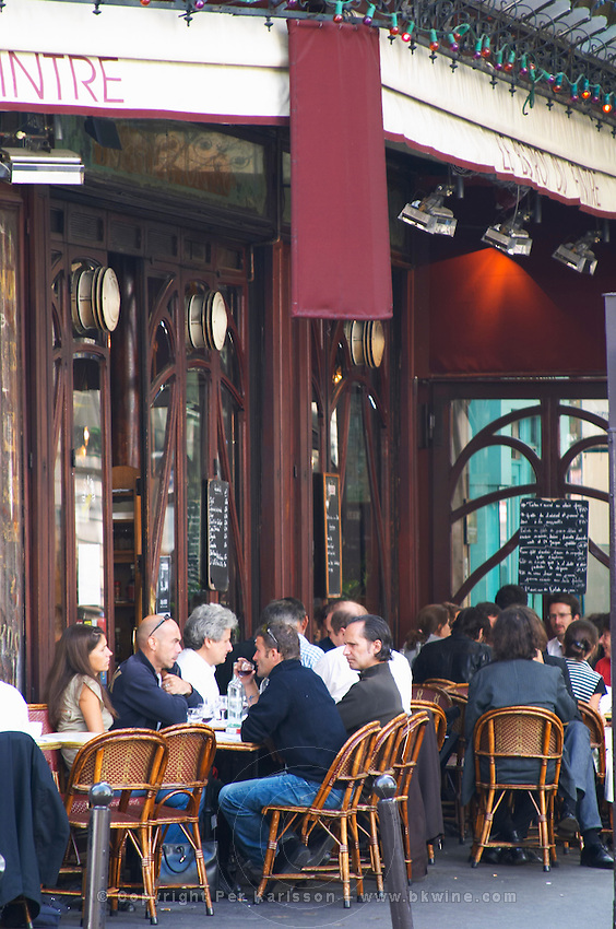 Le Bistrot du Peintre cafe bar terrase outside seating on the sidewalk. People sitting in chairs at tables eating and drinking outside at lunch time. The Bistrot du Peintre is an old fashioned Paris café cafe bar restaurant of art nouveau design with polished brass, mirrors and old signs