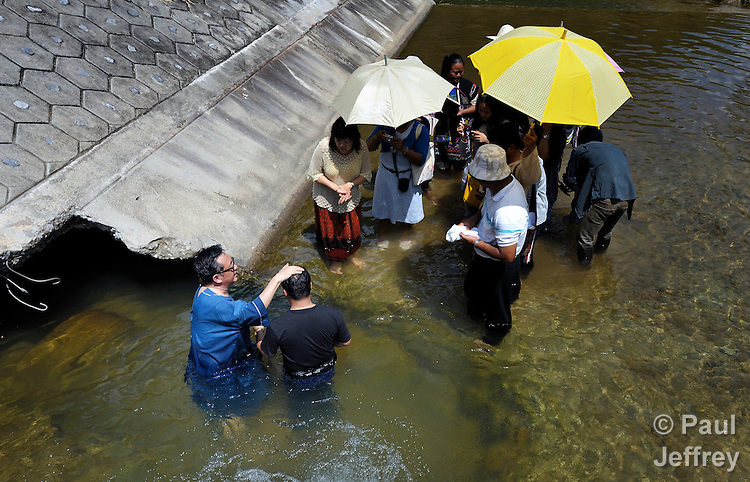 Gary Moon (left), a United Methodist missionary in Thailand, prays with a man before his baptism in a river near Buyer, a small village in northern Thailand populated by indigenous hill tribe people. The man is joining the Pranetta United Methodist Church in the community.