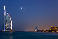 Dubai.  Evening view  of Burj al Arab Hotel, architect W.S. Atkins, an icon of Dubai built in the shape of the sail of a dhow, stands on an island off Jumeirah Beach. In the distance Jumeirah Beach Hotel and Mina a?Salam Hotel. .