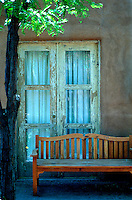 A weathered window on an adobe building and a bench in a courtyard in Santa Fe, New Mexico