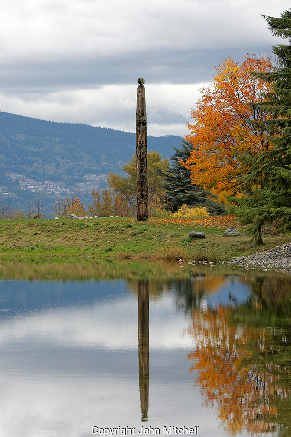 Lone West Coast totem pole reflected in pond, Museum of Anthropology (MOA), Vancouver, BC, Canada