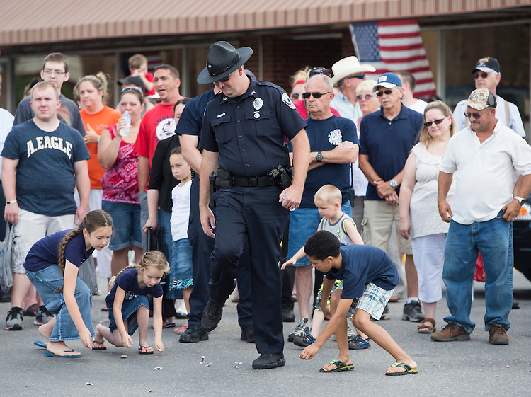 "UNITED STATES - JULY 4: A police officer lifts his feet as children grab candy thrown from parade floats during the Ripley 4th of July Parade in Ripley, W. Va., on July 4, 2014. The parade is billed as ""the USA's largest small town Independence Day Celebration. (Photo By Bill Clark/CQ Roll Call)"