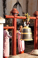 Young nuns use bamboo section to sound bell at Bagan temple-Burma