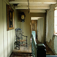 Newly painted wood panelling contrasts with the original crumbling brick and plaster walls on this landing