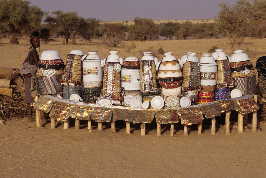 Akadaney, Central Niger, West Africa.  Fulani Nomads.  Woman with her Food Storage and Eating Utensils on Display.
