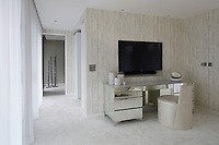 The master suite is a calm and tranquil space in off whites and neutrals. The walls are finished in softly textured vinyl wallpaper with hints of distressed wood cladding. Behind the mirrored dressing table is an open plan dressing room and behind the dressing room is the master en suite.
