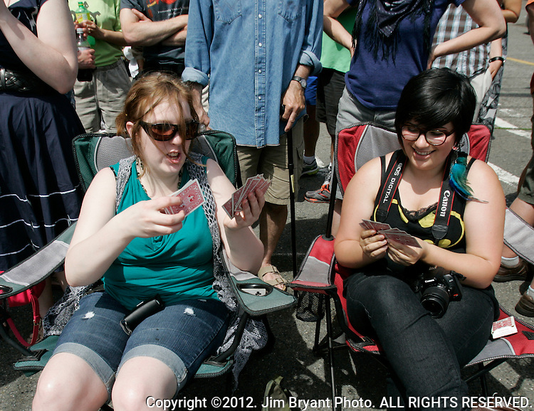 HAnna Czopek, L, and Kat Temin plays a game of Go Fish while waiting for the painted nude bicyclists to ride during the 25th  Annual Fremont Summer Solstice Parade in Seattle on June 22, 2013.     UPI Photo/Jim BryantPainted nude bicyclists  ride during the 25th  Annual Fremont Summer Solstice Parade in Seattle on June 22, 2013.     ©2013.  Jim Bryant.  ALL RIGHTS RESERVED.