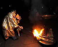 STAFF PHOTO ANDY SHUPE - Dan Barth of Springdale, dressed as the Fire Priest, left, and Sean Thorup, 11, of Fayetteville, dressed as the New Sun, light a bonfire during a celebration of the winter solstice Sunday, Dec. 21, 2014, at the Unitarian Universalist Fellowship of Fayetteville.