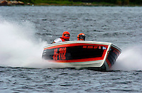 """Shortly before his accident, Bill Mehan (R) pilots his Jersey Speed Skiff """"Miss Align""""."""