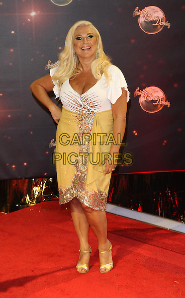 Vanessa Feltz<br /> The red carpet launch for 'Strictly Come Dancing' at Elstree Studios, Borehamwood, England.<br /> September 3rd, 2013<br /> full length gold white yellow top skirt dress hand on hip<br /> CAP/FIN<br /> &copy;Steve Finn/Capital Pictures