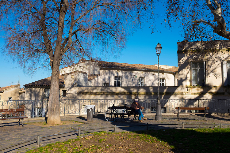 Man sitting on a bench with his bicycle, Place De La Canourgue, Montpellier, France