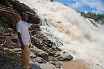 Jegede Andrew, a local, shows off the impressive Gurara Falls.  On the Gurara River in Nigeria's Niger State, Gurara Falls is 200 meters wide, boasting a sheer drop of 30 meters.  An approximately 2-hour drive from the capital of Abuja, it makes a pleasant day trip and picnic stop from the capital.