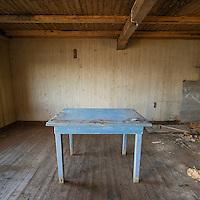 Table in empty room of derelict building, Borgvåg, Lofoten Islands, Norway