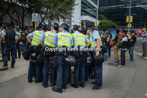 Hong Kong, Government Offices, 28 September 2014<br /> <br /> Middle of the day around the HK government offices. Protesters are prepared against pepper spray and teargas with plastic coats and goggles. Already then the police tries to block the entry and exit points of the area.<br /> Police huddled together<br /> <br /> Photo Kees Metselaar