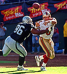 Oakland Raiders vs. San Francisco 49ers at Oakland Alameda County Coliseum Monday, August 30, 1999.  49ers beat Raiders  16-8 in a preseason game.  Oakland Raiders defensive end Darrell Russell (96) rushes San Francisco 49ers quarterback Steve Young (8).