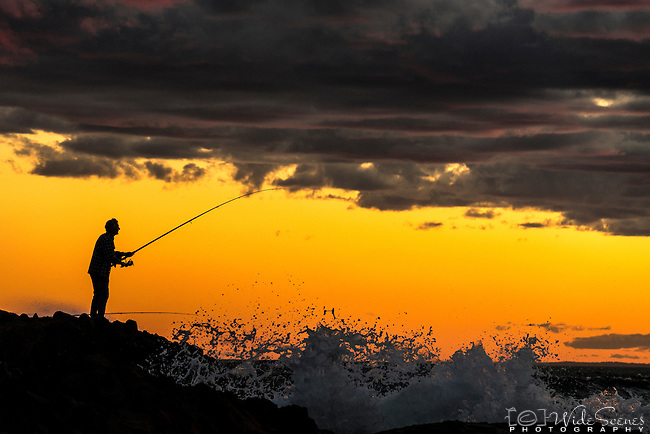 Silhouette of Fisherman on the rocks at Stockton Beach, Anna Bay, NSW, Australia
