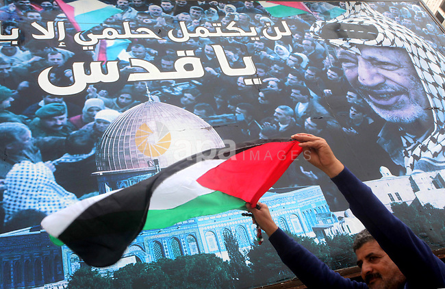 A Palestinian man holds national flag during a rally to support reconciliation between rival Palestinian factions in Gaza city on 04 Dec, 2012. Palestinian president Mahmud Abbas pledged Sunday to resume efforts at reconciliation between rival Palestinian factions as he returned from a successful bid for upgraded UN status. Photo by Ashraf Amra