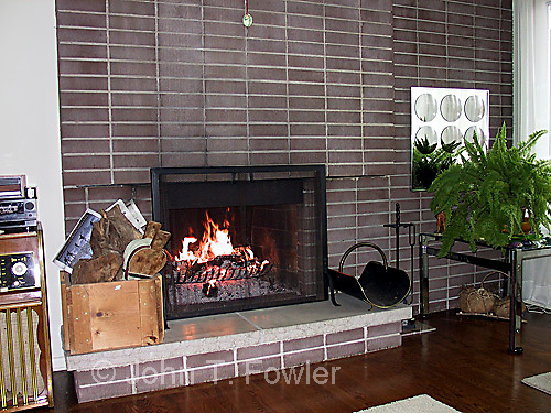 Brick fireplace in modern home with fire burning