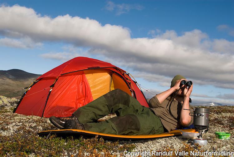 Mann ligger utenfor telt og speider i kikkert ---- Man outside tent looking in binoculars