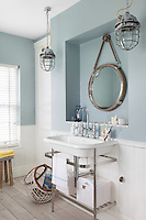 A nautical themed bathroom, with tongue and groove panelling below pale blue walls, metal light fittings and a porthole-like mirror above the wash basin