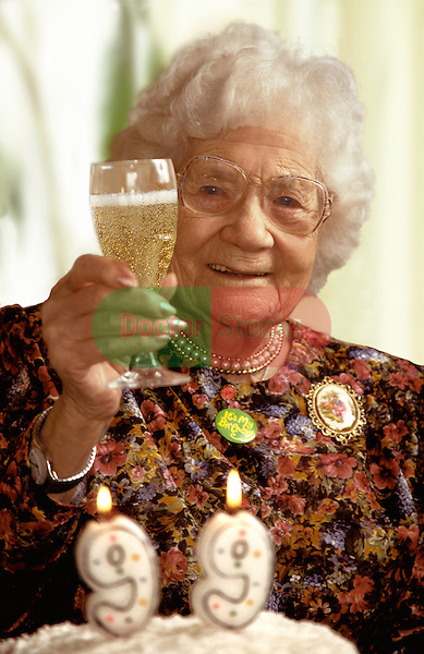 Elderly woman enjoying a glass of Champagne on her 99th birthday