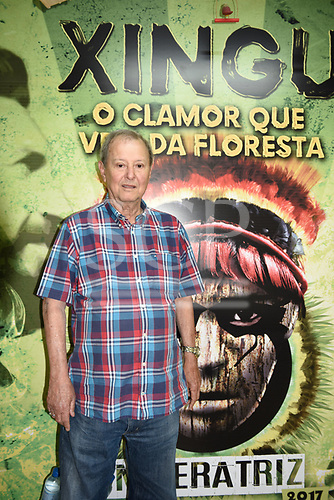 "Rio de Janeiro, Brazil. Imperatriz Leopoldinense samba school; preparations for carnival. Luiz Pacheco Dumond, President of the Samba School, stands in front of a poster which says ""Xingu, the call which comes from the forest""."