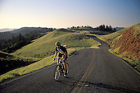 Male bicyclist on curving two-lane road through rolling green hills in spring, Bolinas Ridge, Mount Tamalpais, Marin County, California