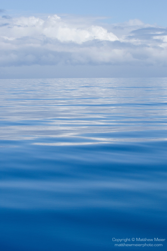 Somosomo Strait, Taveuni, Fiji; white puffy clouds reflect in the ripples on the water's surface