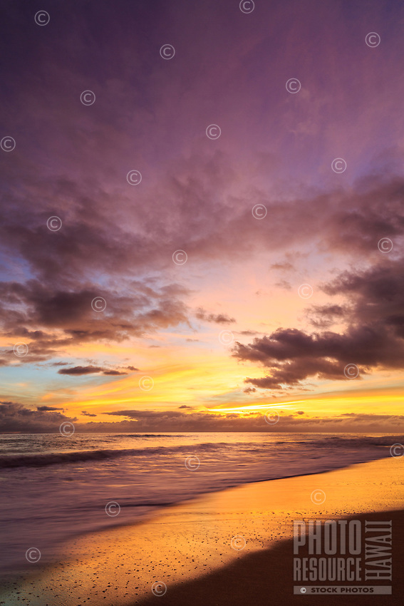 Purple and gold fill the sky at sunset as the surf washes onto the sandy shores of Kekaha Beach, Kaua'i.