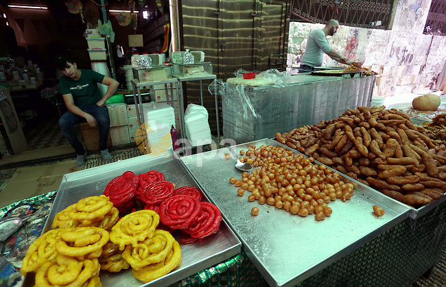 A Palestinian vendor preparers a traditional sweets at a market on the Muslim holy fasting month of Ramadan in the Old City of the West Bank town of Nablus, on June 13, 2017. Ramadan is sacred to Muslims because it is during that month that tradition says the Koran was revealed to the Prophet Mohammed. The fast is one of the five main religious obligations under Islam. More than 1.5 billion Muslims around the world will mark the month, during which believers abstain from eating, drinking, smoking and having sex from dawn until sunset. Photo by Ayman Ameen
