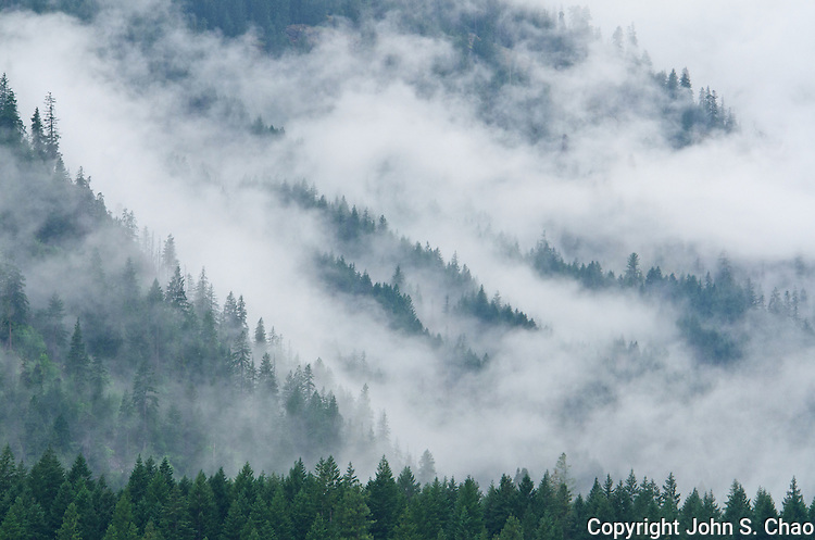 Clouds and mist brush forested mountain ridges in Stehekin, North Cascades National Park, Washington State