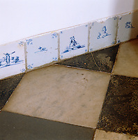 Antique blue and white tiles are laid as skirting against a black and white marble floor in the entrance hall