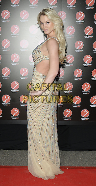 AMY GUY .At the Sport Industry Awards, Battersea Evolution, London, England, UK, .May 13th 2010..arrivals full length gold sequined silver sequin dress cut out hand on hip long maxi  side looking over shoulder back rear behind .CAP/CAN.©Can Nguyen/Capital Pictures.